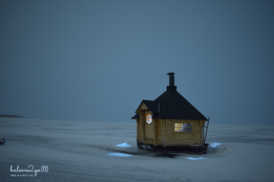 Wooden house on frozen lake